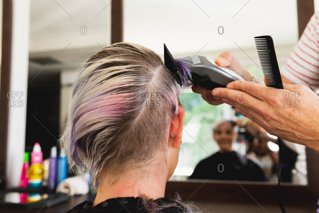 Rear view close up of a middle aged Caucasian male hairdresser and a young Caucasian woman having her hair trimmed in a hair salon, reflected in a mirror