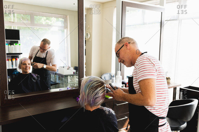 Side view of a middle aged Caucasian male hairdresser and a young Caucasian woman having her hair trimmed in a hair salon, reflected in a mirror