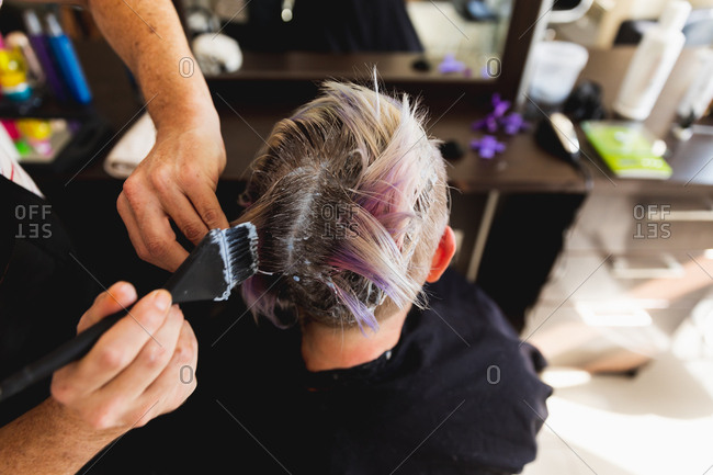 Rear view close up of a middle aged Caucasian male hairdresser and a young Caucasian woman having her hair colored in a hair salon