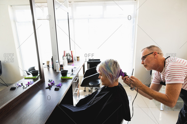 Side view of a middle aged Caucasian male hairdresser and a young Caucasian woman having her hair trimmed in a hair salon