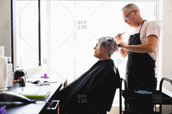 Side view of a middle aged Caucasian male hairdresser and a young Caucasian woman having her hair colored in a hair salon