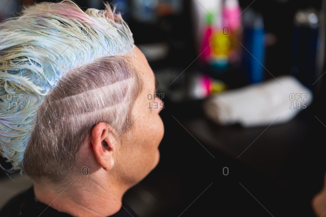 Side view close up of a young Caucasian woman having her hair styled in a hair salon