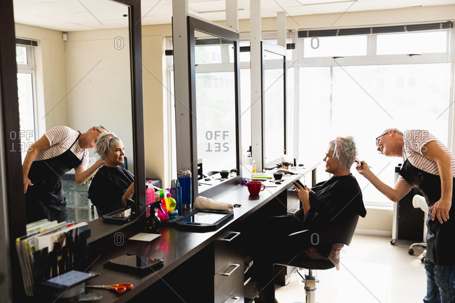 Side view of a middle aged Caucasian male hairdresser and a young Caucasian woman having her hair colored in a hair salon, reflected in a mirror