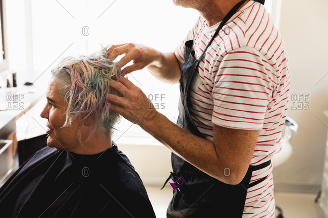Side view close up of a middle aged Caucasian male hairdresser and a young Caucasian woman having her hair colored in a hair salon