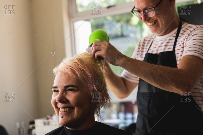 Side view close up of a middle aged Caucasian male hairdresser and a young Caucasian woman having her hair blow dried in a hair salon