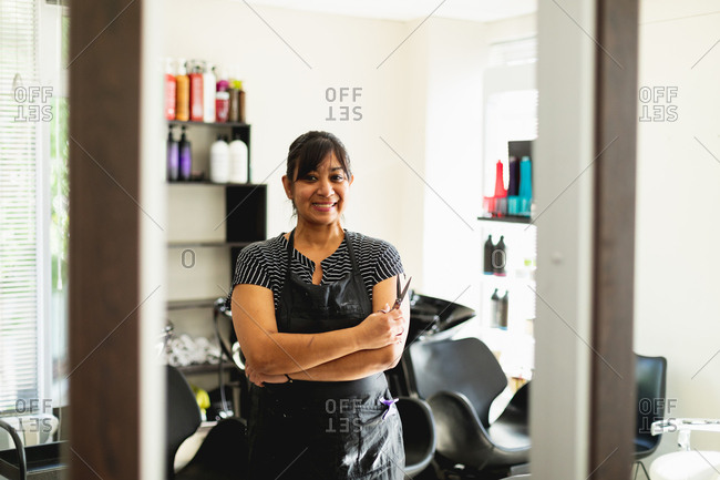Portrait of a middle aged mixed race female hairdresser smiling to camera with her arms crossed in a hair salon