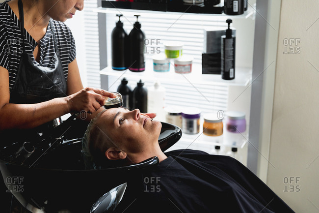 Side view of a middle aged mixed race female hairdresser and a young Caucasian woman having her hair washed in a hair salon