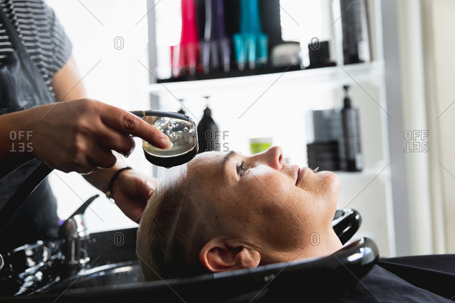 Side view close up of a middle aged mixed race female hairdresser and a young Caucasian woman having her hair washed in a hair salon