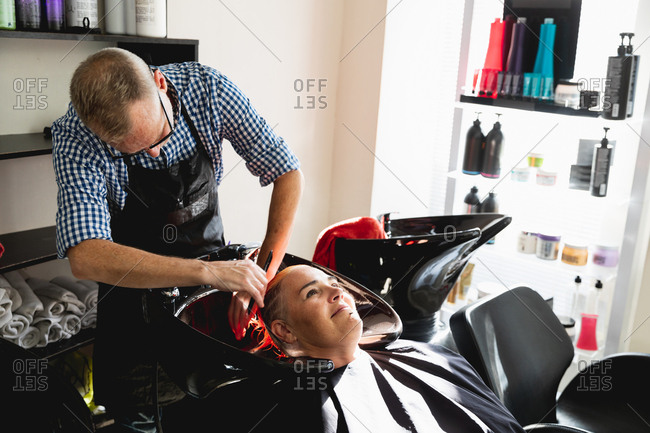 Front view of a middle aged Caucasian male hairdresser and a young Caucasian woman having her hair washed in a hair salon