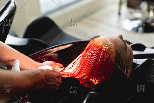 Rear view close up of a middle aged Caucasian male hairdresser and a young Caucasian woman having her hair colored bright red, washed and combed in a hair salon