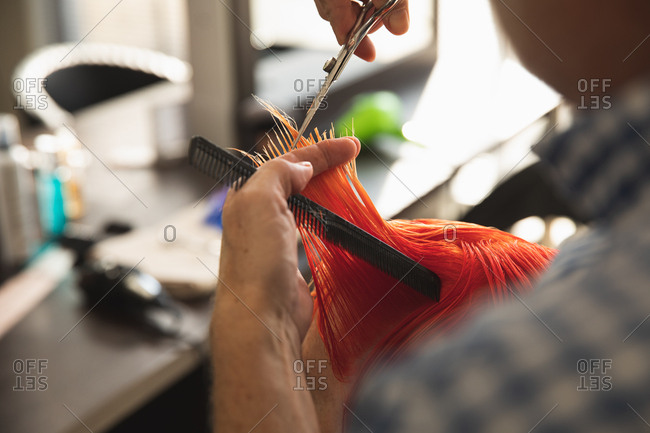 Close up of a middle aged Caucasian male hairdresser and a young Caucasian woman having her hair colored bright red and cut in a hair salon