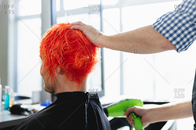 Rear view close up of a middle aged Caucasian male hairdresser and a young Caucasian woman having her hair colored bright red and blow dried in a hair salon