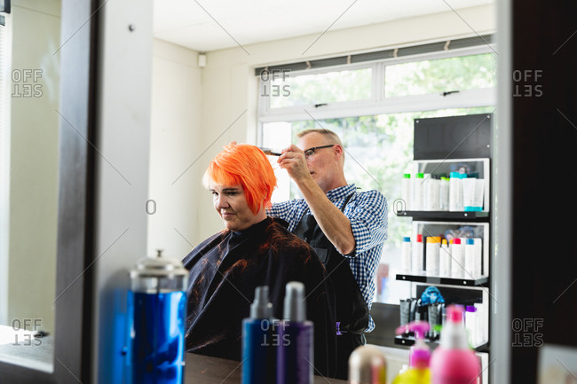 Side view of a middle aged Caucasian male hairdresser and a young Caucasian woman having her hair colored bright red in a hair salon, reflected in a mirror