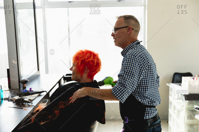 Side view of a middle aged Caucasian male hairdresser and a young Caucasian woman having her hair colored bright red and blow dried in a hair salon