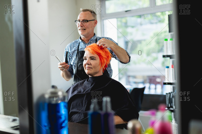 Front view of a middle aged Caucasian male hairdresser and a young Caucasian woman having her hair colored bright red and cut in a hair salon, reflected in a mirror