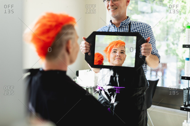 Front view of a middle aged Caucasian male hairdresser and a young Caucasian woman having her hair colored bright red and shown in a hand held mirror in a hair salon