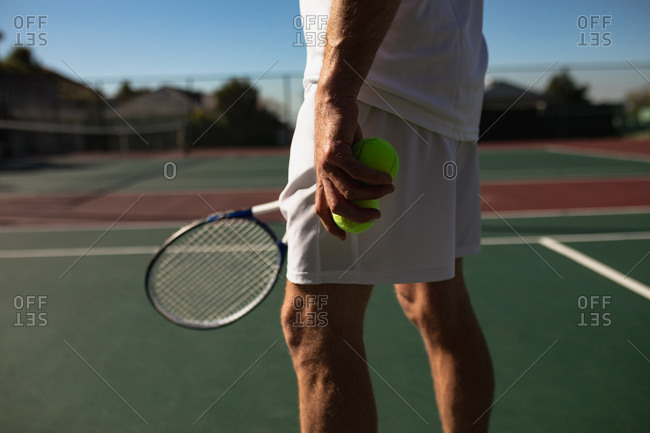 Side view close up of a young Caucasian man playing tennis on a sunny day, holding a racket and balls