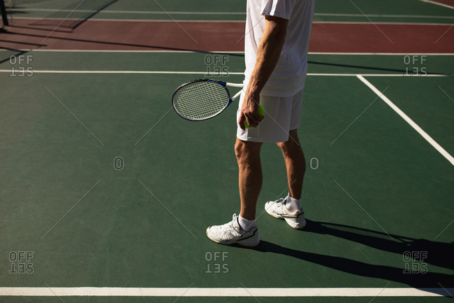 Side view of a young Caucasian man playing tennis on a sunny day, holding a racket and balls