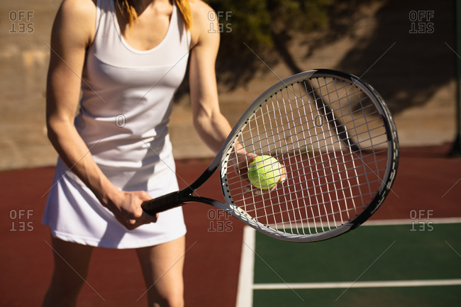 Front view close up of a young Caucasian woman playing tennis on a sunny day, preparing to serve