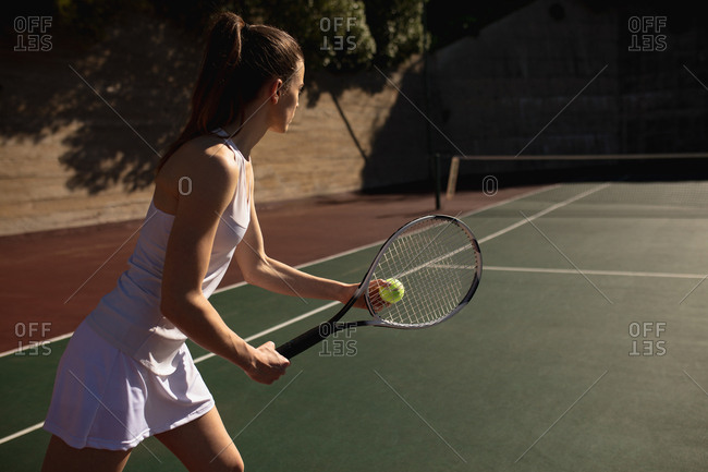 Side view of a young Caucasian woman playing tennis on a sunny day, preparing to serve with a wall behind her