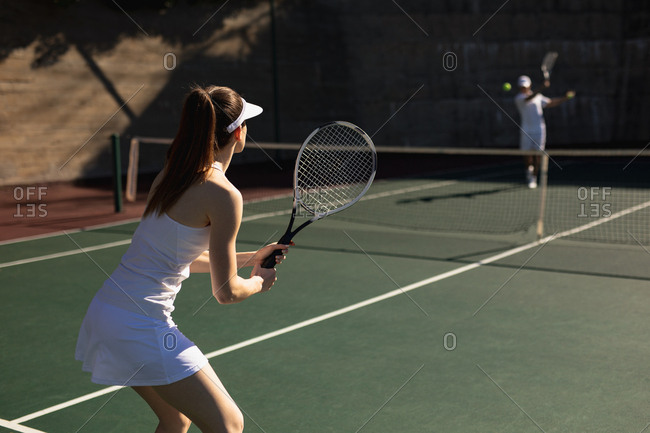 Rear view of a young Caucasian woman and a man playing tennis on a sunny day, man hitting a ball