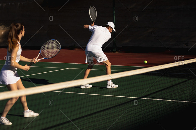 Side view of a young Caucasian woman and a man playing tennis on a sunny day, man returning a ball
