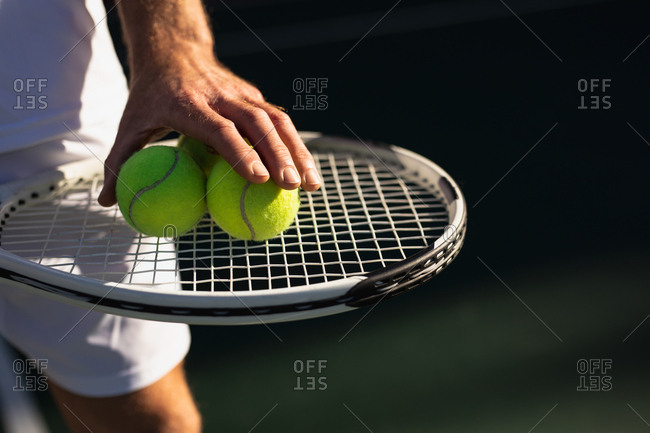 Front close up of a young Caucasian man playing tennis on a sunny day, holding a racket and balls