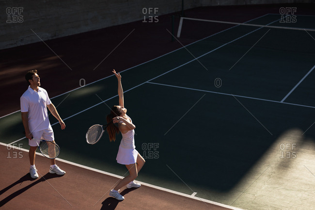 Side view of a young Caucasian woman and a man playing tennis on a sunny day, woman serving