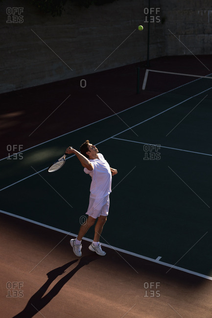 Side view of a young Caucasian man playing tennis, serving