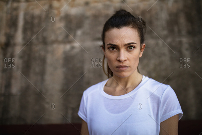 Portrait of a young Caucasian female tennis player, wall in a background