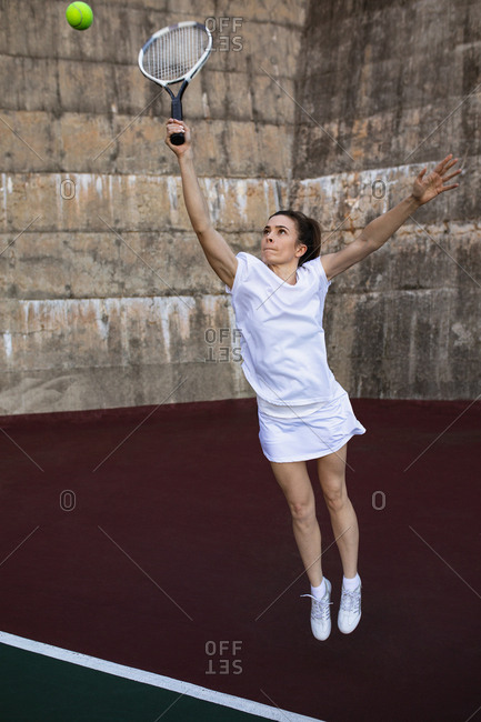 Front view of a young Caucasian woman playing tennis, holding a racket and jumping to the ball with a wall behind her