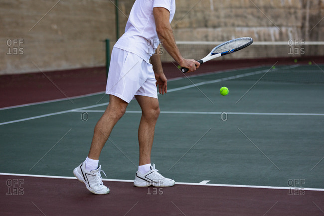 Side view of a young Caucasian man playing tennis, preparing to serve with a wall in a background