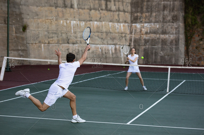 Rear view of a young Caucasian woman and a man playing tennis, man returning the ball with a wall in the background