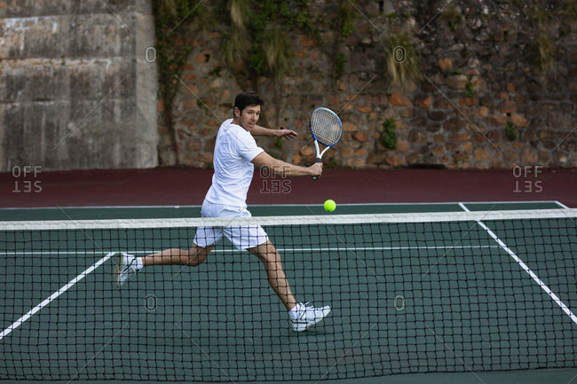 Side view of a young Caucasian man playing tennis, running up to a ball with a wall behind him
