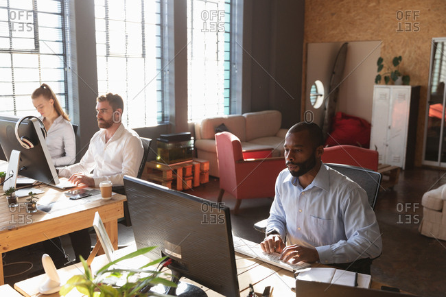 Front view of a young African American man and a young Caucasian woman and man sitting at desks using computers in a creative office
