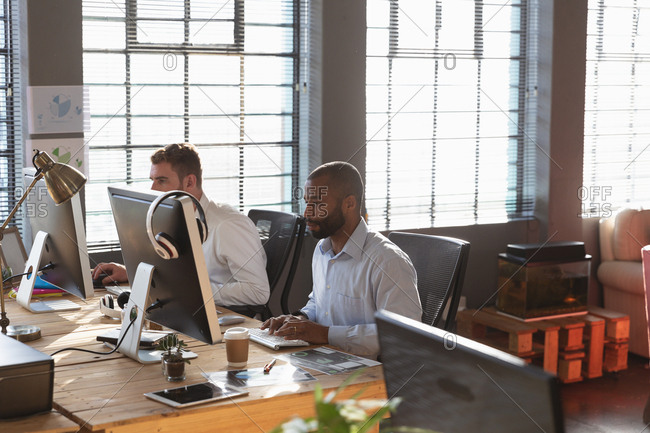 Side view of a young African American man and a young Caucasian man sitting at a desk using computers in a creative office