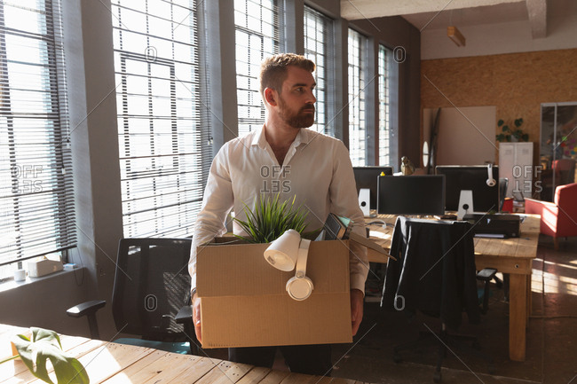 Front view close up of a young Caucasian man standing at a desk by a window in a creative office holding a cardboard box of his belongings having cleared his desk to leave