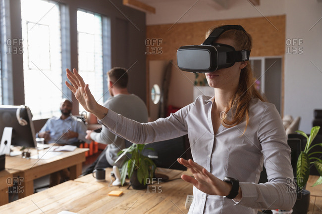 Front view close up of a young Caucasian woman wearing a VR headset standing with arms outstretched and hands out in a creative office, with colleagues working in the background