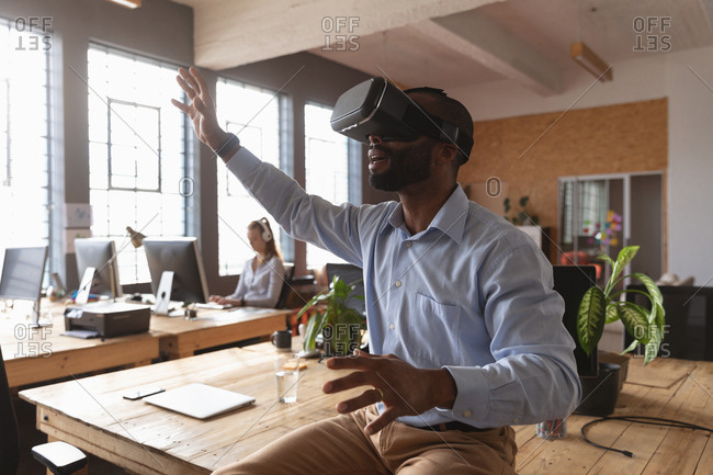 Side view close up of a young African American man sitting on a desk wearing a VR headset with his arms outstretched and hands out in a creative office, a female colleague working in the background