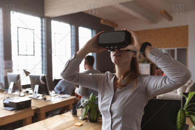 Front view close up of a young Caucasian woman wearing a VR headset standing and looking up in a creative office, with colleagues working in the background
