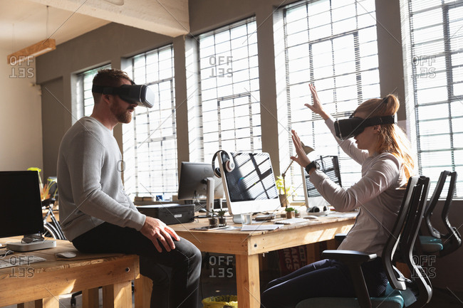 Side view close up of a young Caucasian man sitting on a desk and a young Caucasian woman sitting on a chair both wearing a VR headsets in a creative office