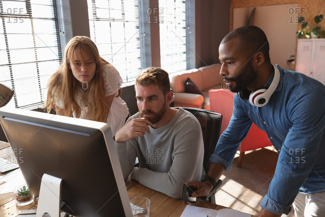 Front view close up of a young African American man and a young Caucasian woman standing either side of a young Caucasian male colleague sitting at a desk using a computer, looking at his monitor together and talking in a creative office