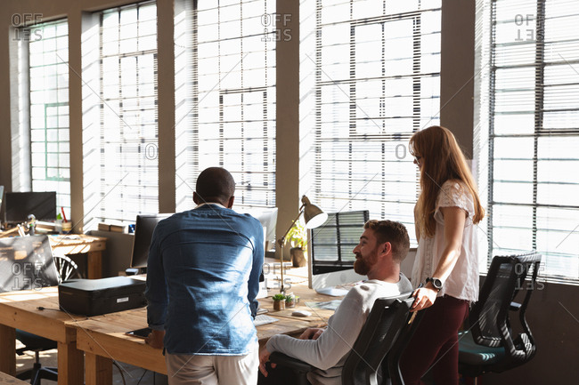 Rear view of a young African American man and a young Caucasian woman standing either side of a young Caucasian male colleague sitting at a desk using a computer, looking at his monitor together and talking in a creative office
