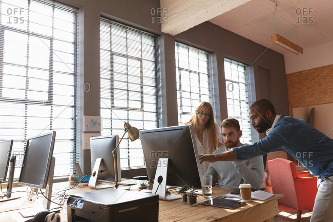 Front view close up of a young African American man and a young Caucasian woman standing either side of a young Caucasian male colleague sitting at a desk using computer, looking at his monitor together and talking in a creative office