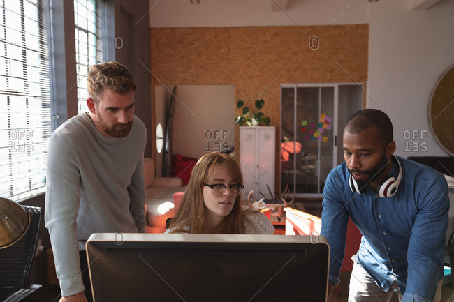 Front view close up of a young African American man and a young Caucasian man standing either side of a young Caucasian female colleague sitting at a desk using a computer, looking at her monitor together and talking in a creative office