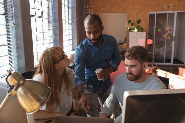 Front view close up of a young African American man standing holding a cup of coffee talking with a young Caucasian female and male colleague sitting at a desk using a computer in a creative office