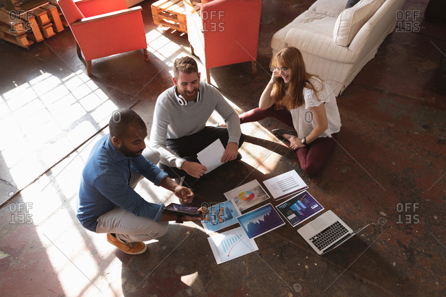 High angle view of a young African American man and a young Caucasian man and woman sitting on the floor looking at visuals together, using a laptop computer and talking while brainstorming in a creative office
