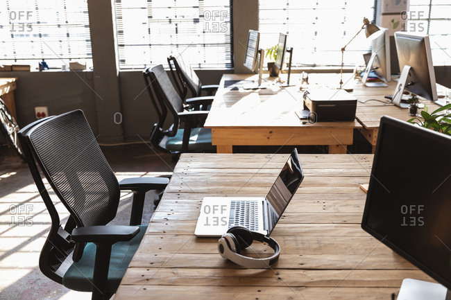 Side view of chairs at desks with computer monitors, a laptop and a pair of headphones on them in a creative office space lit by sunlight from large windows in the background