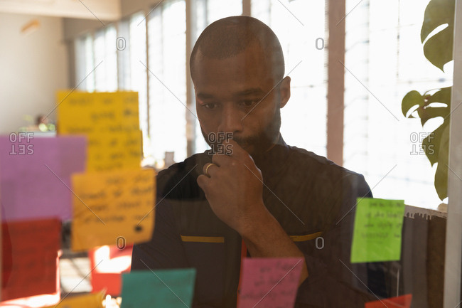 Front view close up of a young African American man reading notes on a glass wall and thinking during a team brainstorm session at a creative office, seen through glass wall