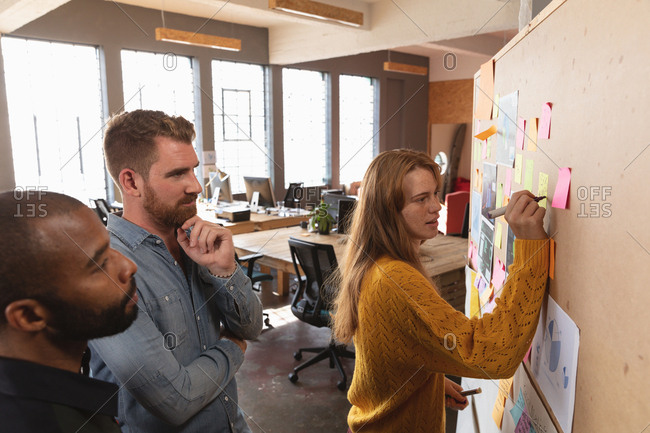 Side view close up of a young African American man and a young Caucasian man standing and watching their young Caucasian female colleague writing a note on an ideas board during a team brainstorm session at a creative office
